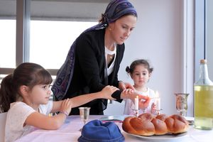 Jewish mother and daughters light Sabbath candles, with challah
