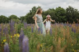 Mother and daughter walking through meadow