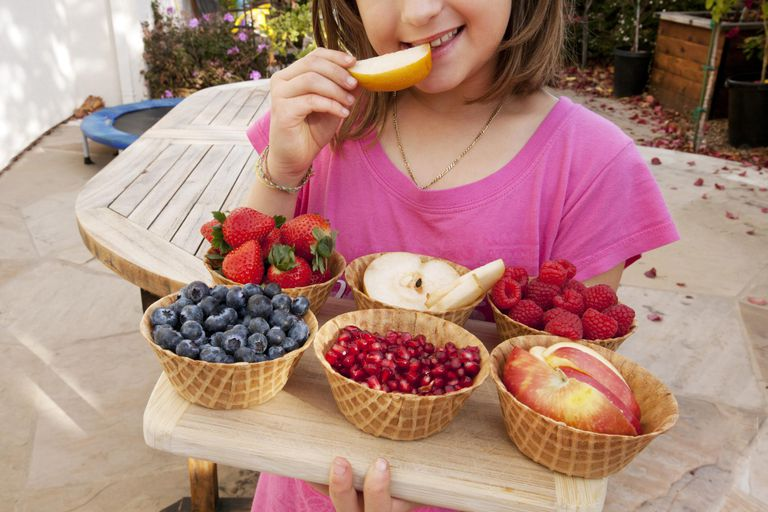 Young girl eating fresh fruits