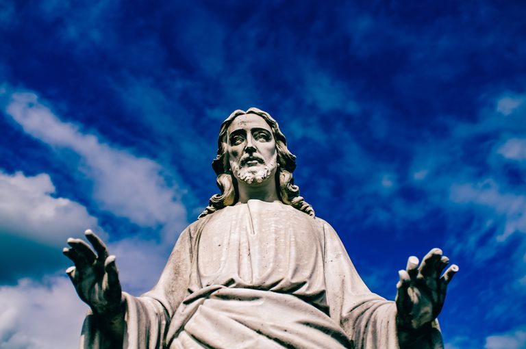 Low angle view of Jesus statue against blue sky
