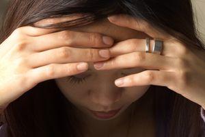 Woman holding her head in her hands in suffering