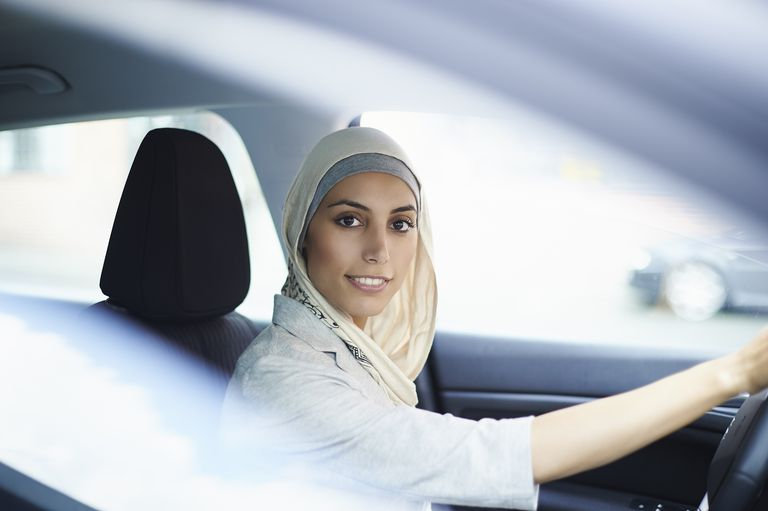 Portrait of young businesswoman wearing hijab driving car