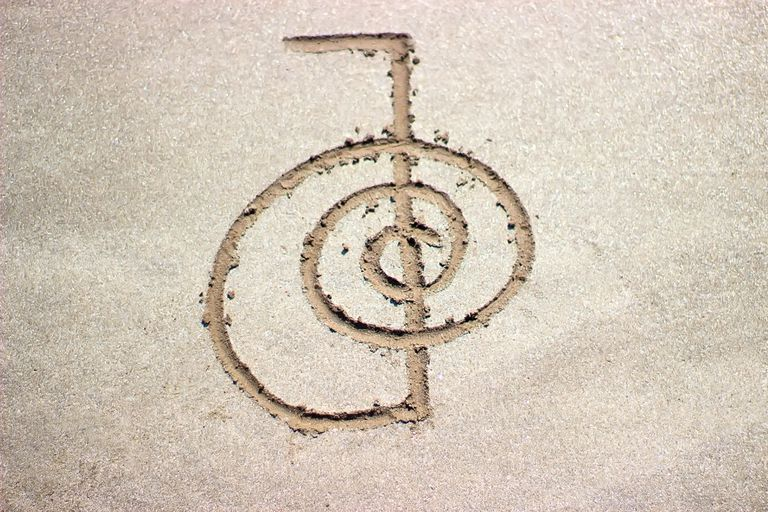 Reiki healing symbol cho ku rei on sand, an alternative medicine concept.