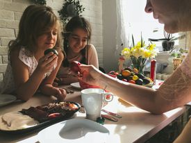 Family coloring Serbian orthodox easter eggs at table with food
