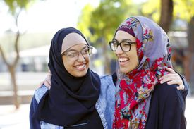 A Muslim mother and daughter laughing in the park
