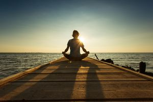 Joyful man meditating on pontoon over a lake at sunrise