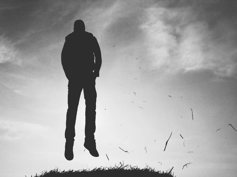 Silhouette Man Levitating Above Grass Against Sky