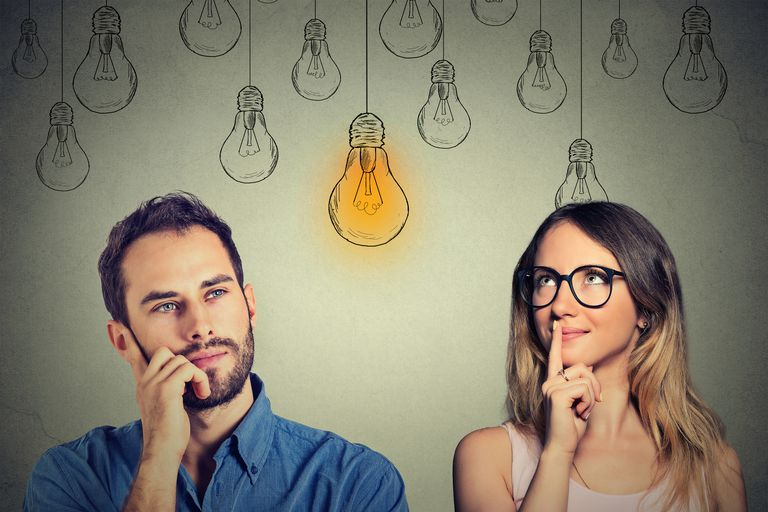 man and woman looking at bright light bulb