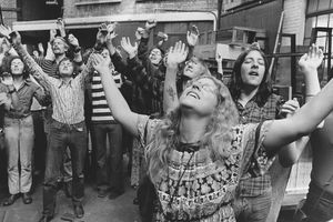 A gathering of Children of God cult members participate in a worship scene with their arms raised.
