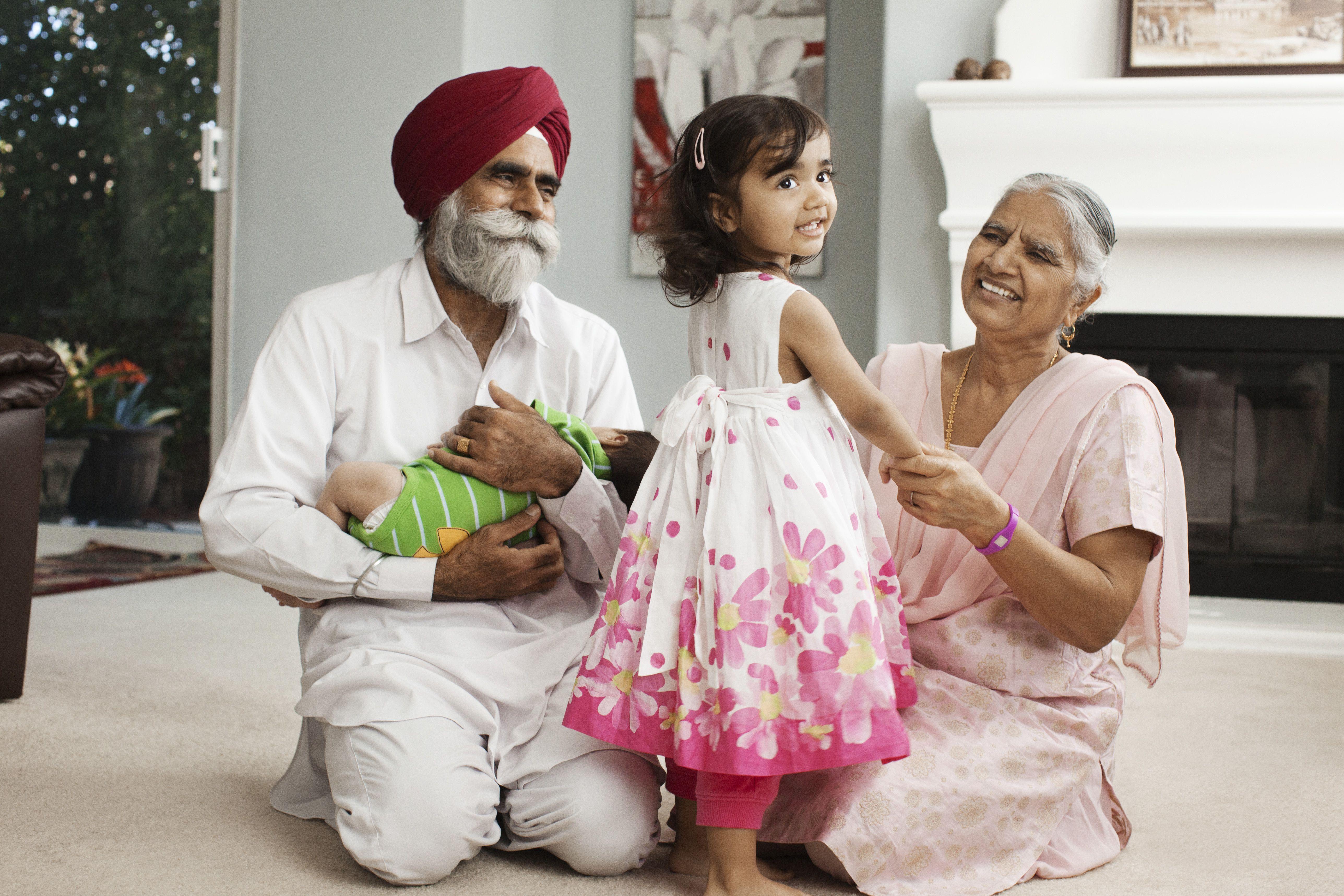 Asian grandparents in living room with grandchildren