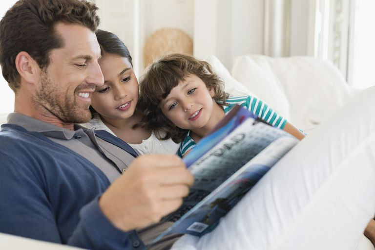 Man reading a magazine with his children