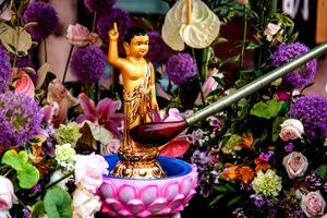 Ladle pouring Liquid On Buddha Figurine During Festival