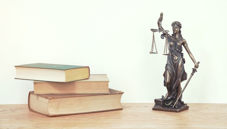 Close-Up Of Books And Lady Justice On Table Against Wall