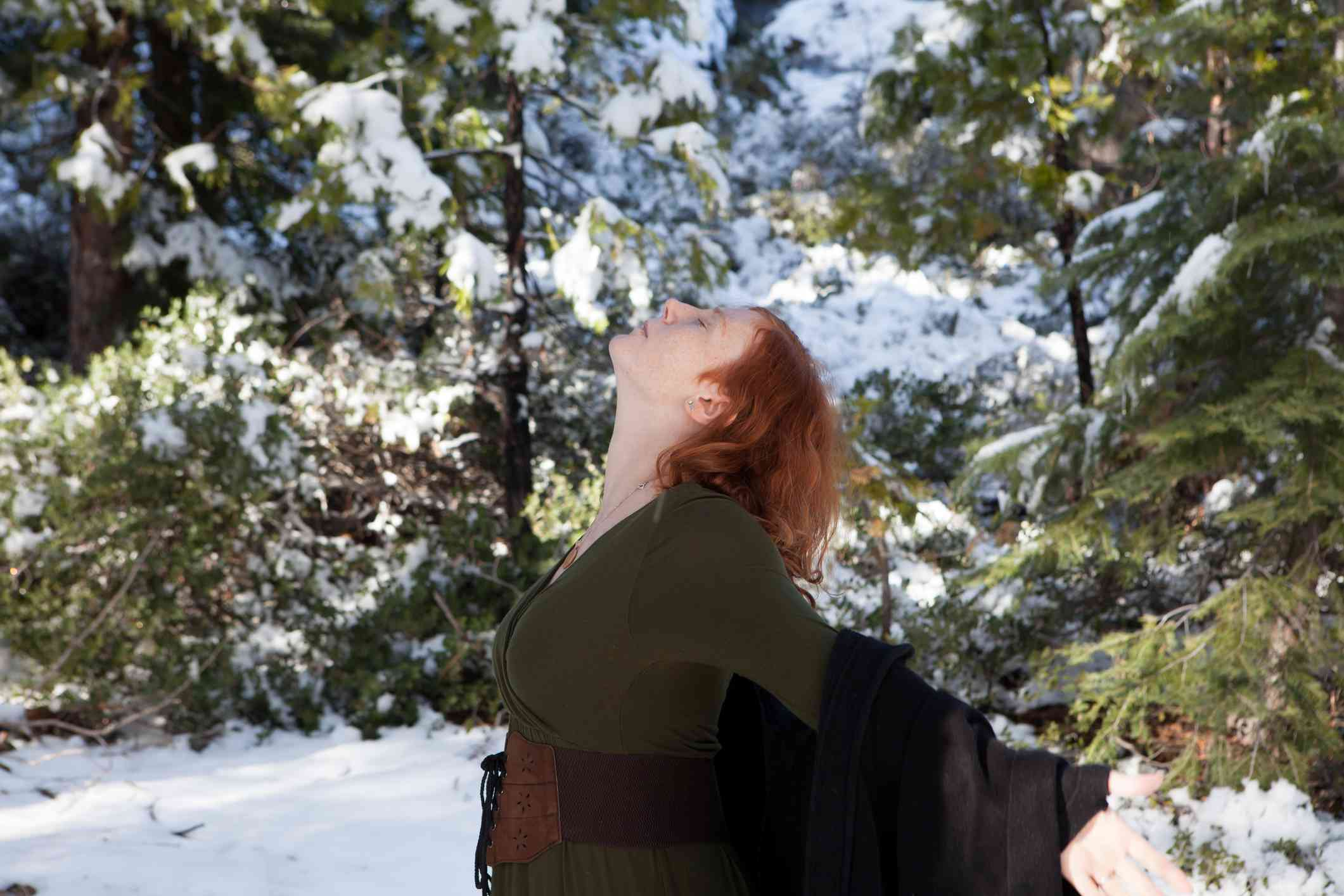 Woman holding ritual in snowy woods
