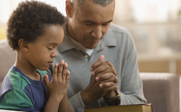 Father and son praying together with the Bible.