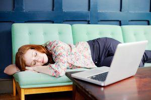 Woman asleep on sofa with laptop