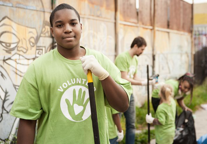 A young man holding a shovel doing volunteer work