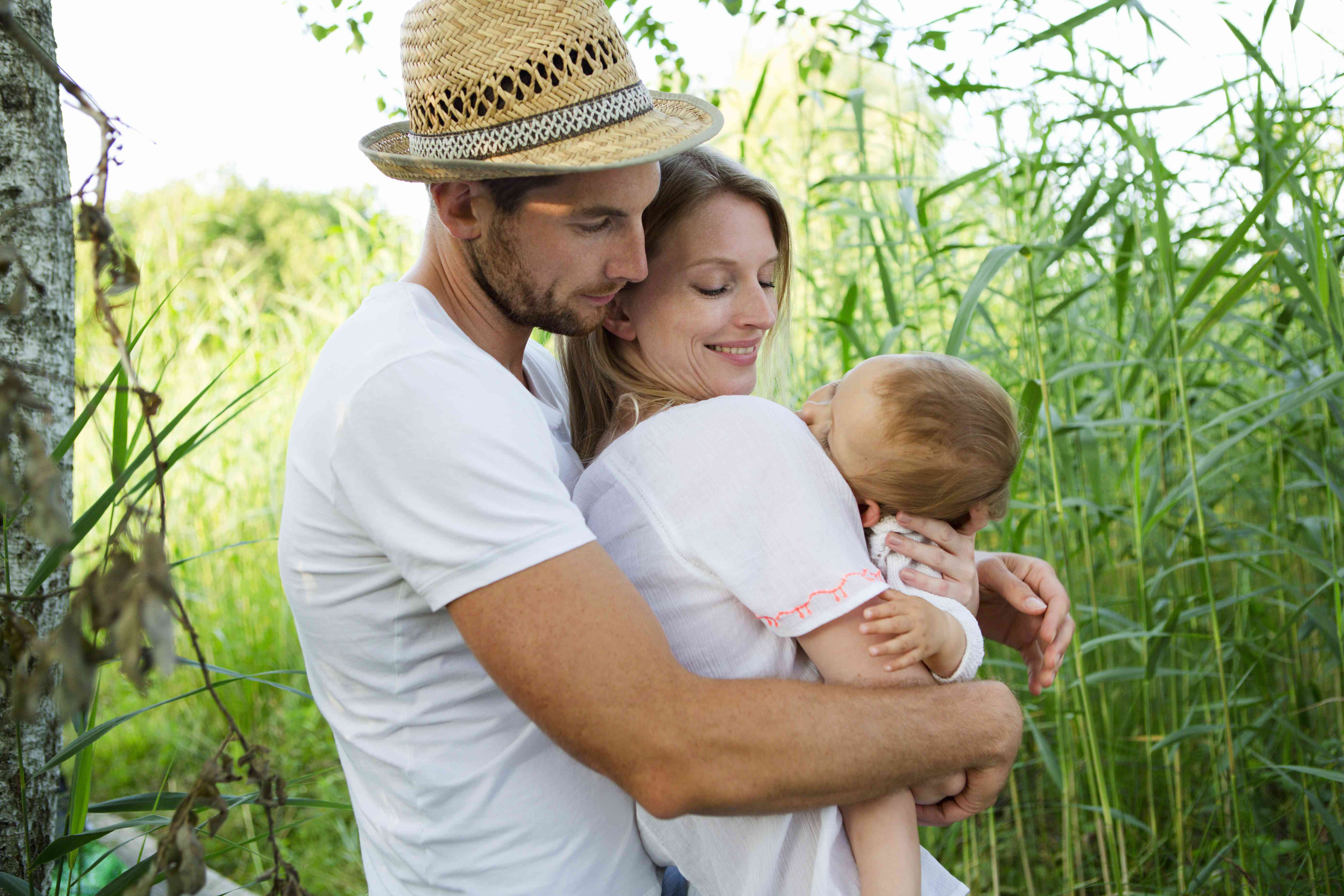 Mid adult couple and baby daughter with arms around each other in reeds