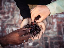 Directly Above Shot Of Hands Holding Date Fruit During Ramadan
