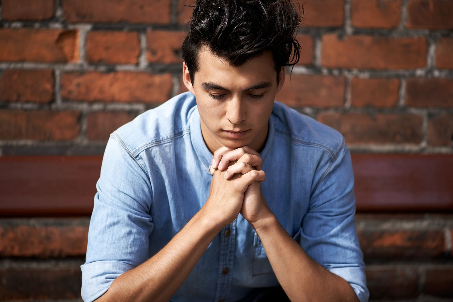 A young man praying for the answers.