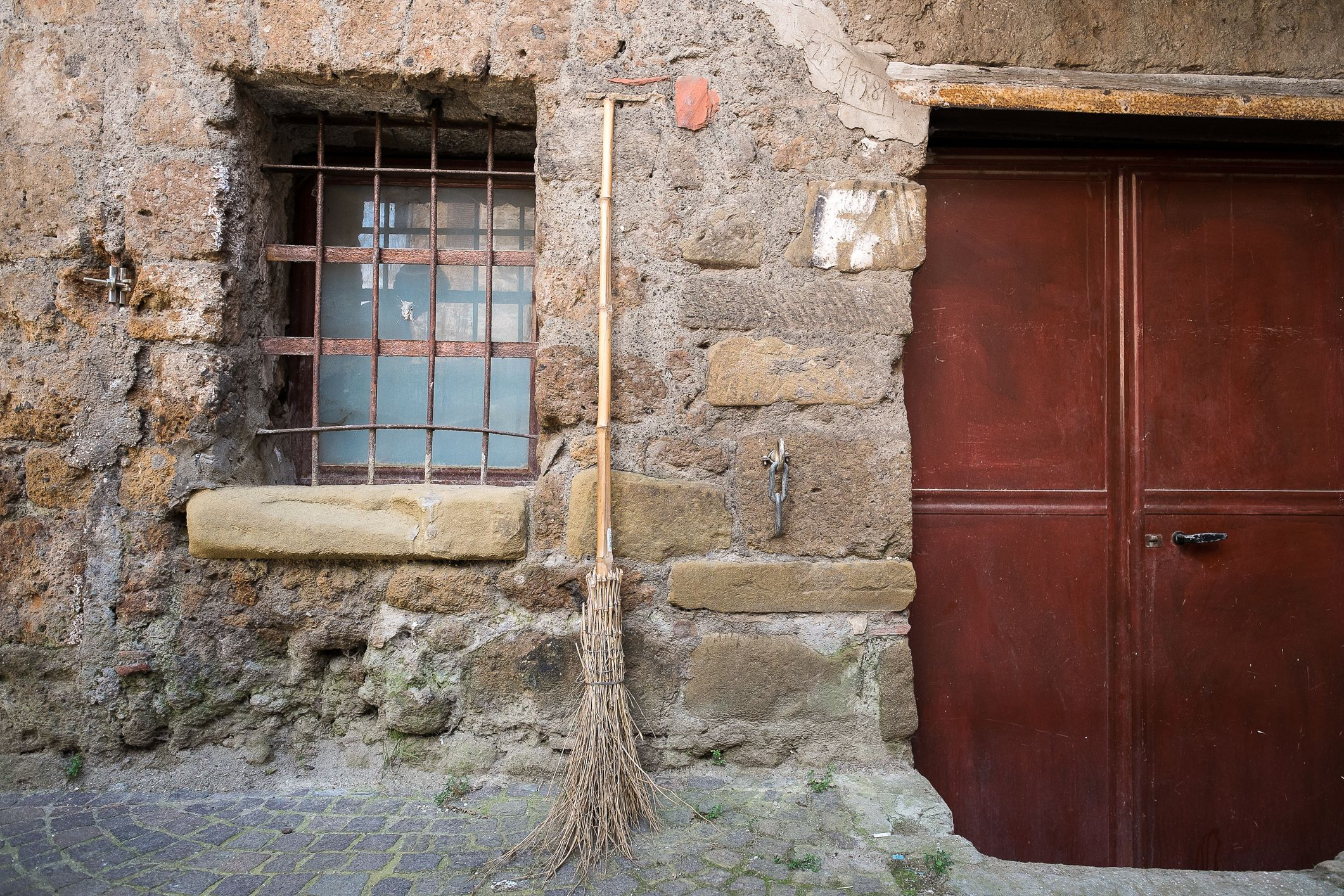 A straw broom rests against an old stone wall
