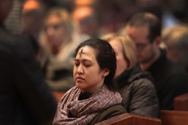 Woman sitting in cathedral after receiving her ash cross.