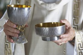 Priest holding goblet and communion bowl