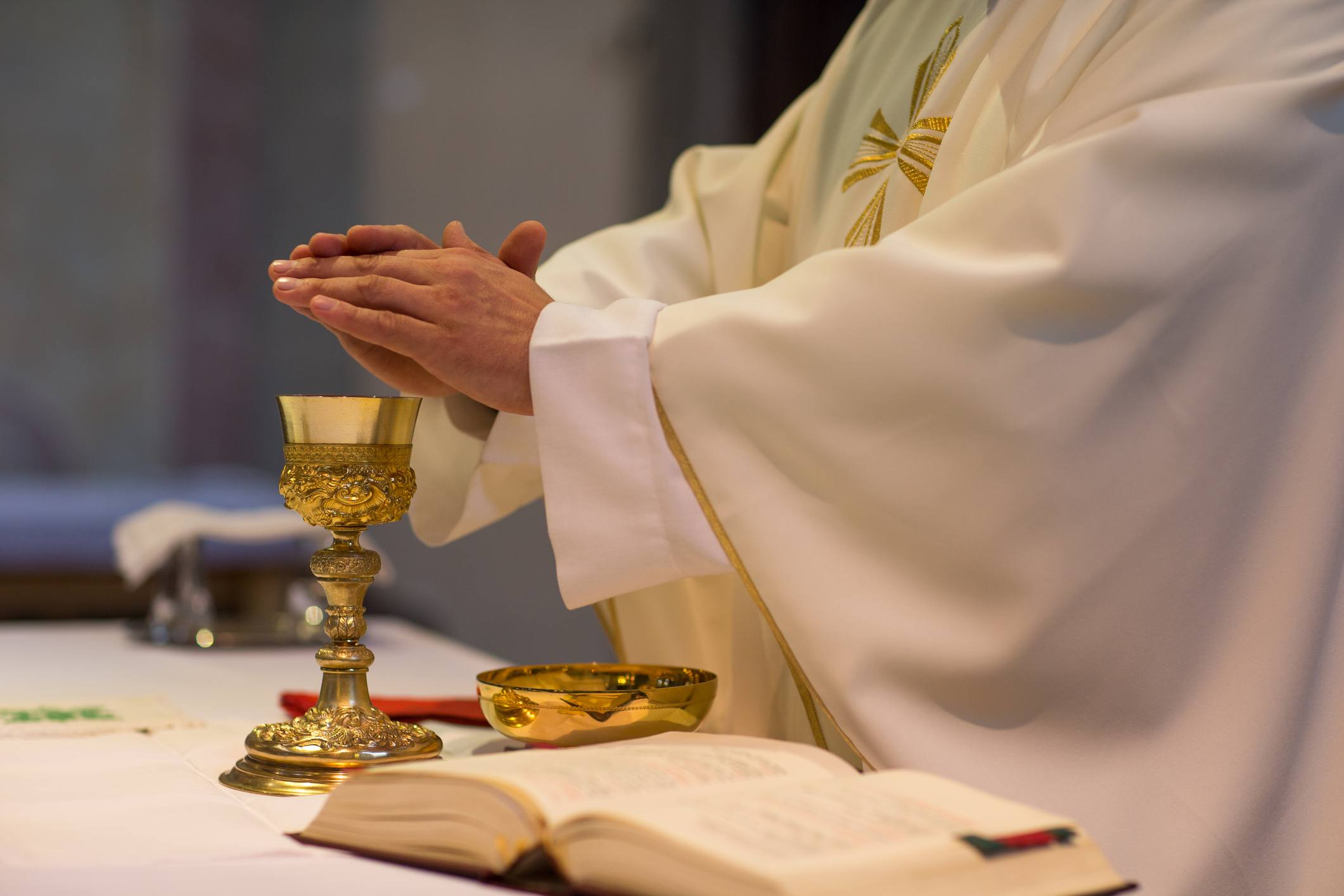 Close up of priest's hands over gold goblet next to bible