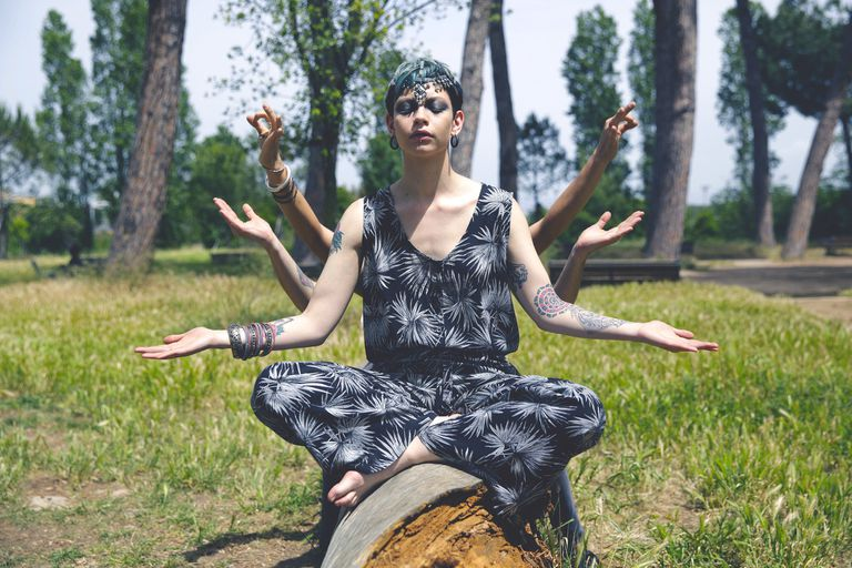Young Woman Gesturing Mudra While Sitting On Fallen Tree