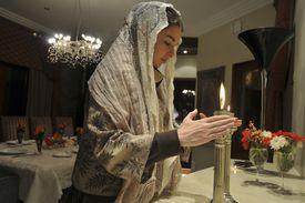 A woman lights Shabbat candles.