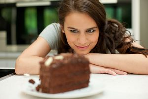 Girl looking at cake on a table.