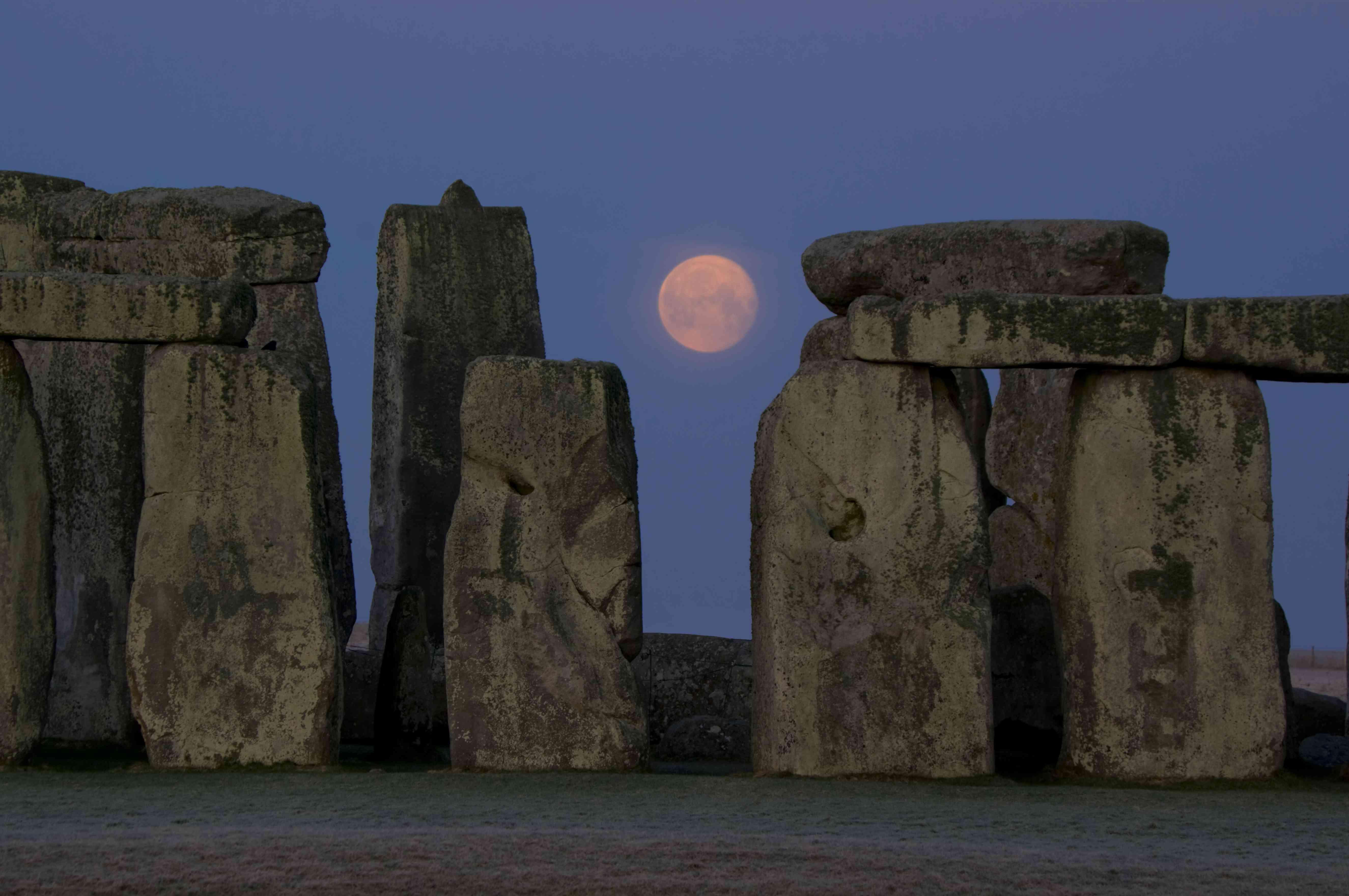 Moon descends between stones of Stonehenge