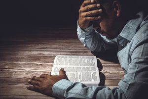 Stressed man reading Bible
