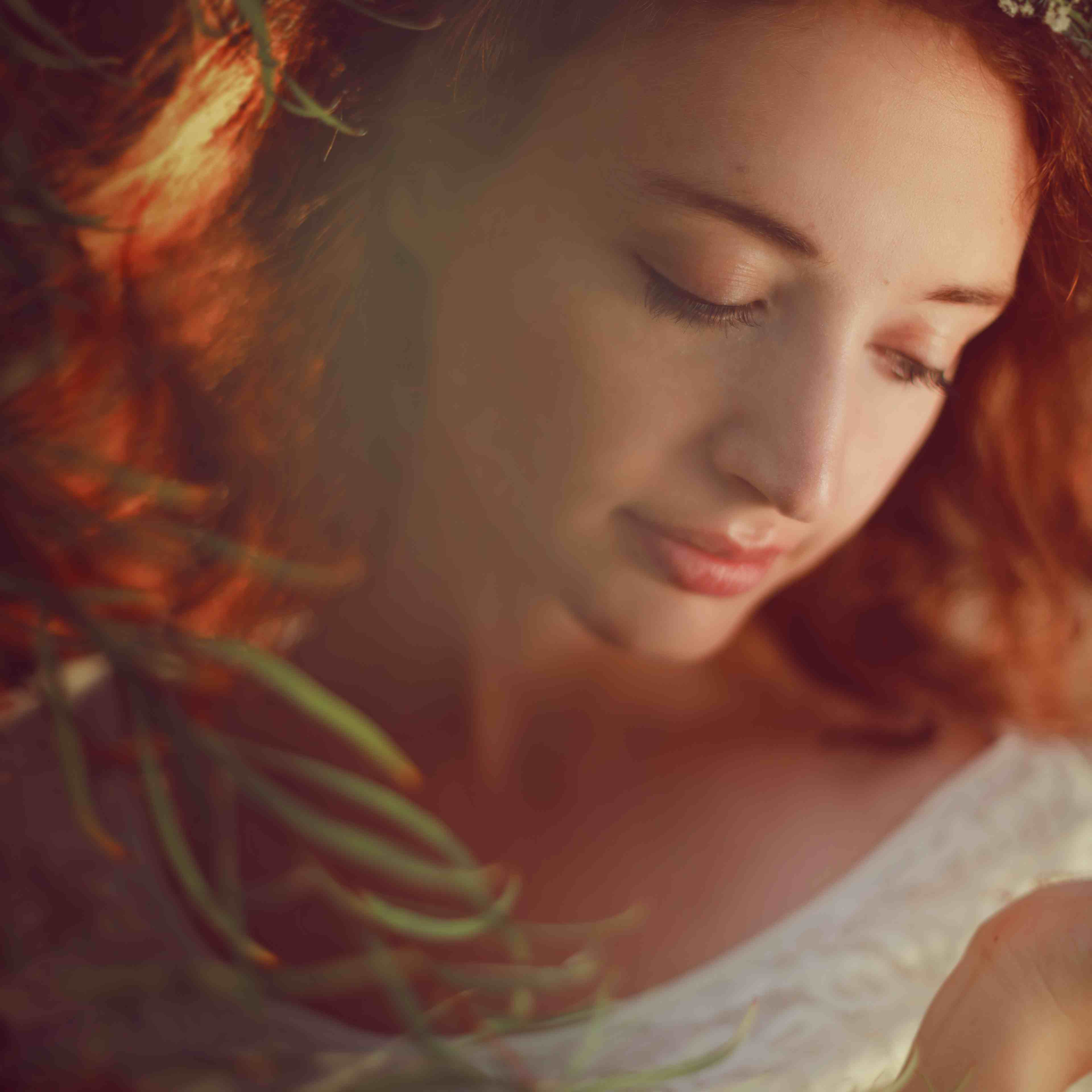 Redhead in white with flower crown looks down