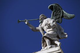 Venice, Veneto, Italy; An archangel with a trumpet on one of the churches in the city