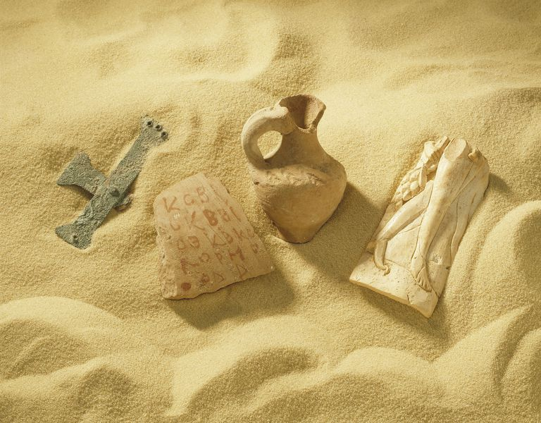 Archaeological artifacts found in Israel, partially embedded in sand