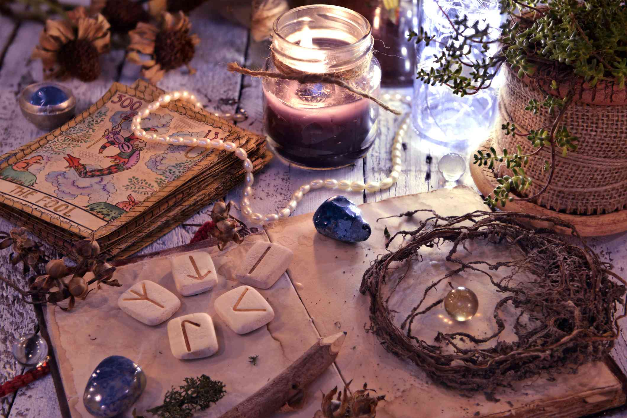 Old tarot cards deck, runes and dried roots with book on table