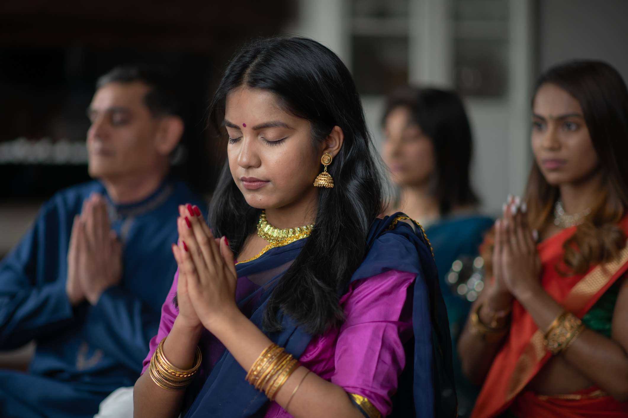 Indian family praying together, celebrating Diwali.
