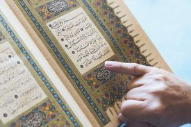 A man reading from the koran with his finger pointing to the text; turkey