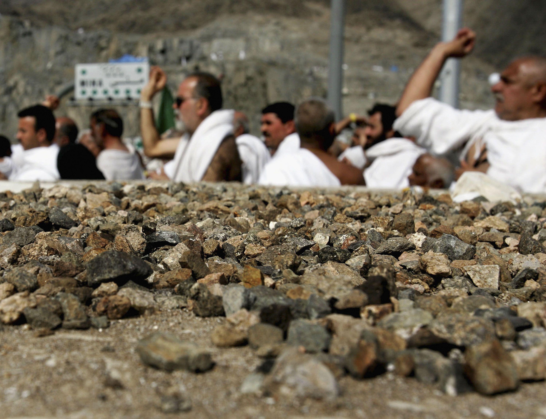 Muslim Pilgrims throw stones at a pillar as part of Hajj