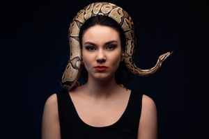 Close up portrait of woman with snake on head