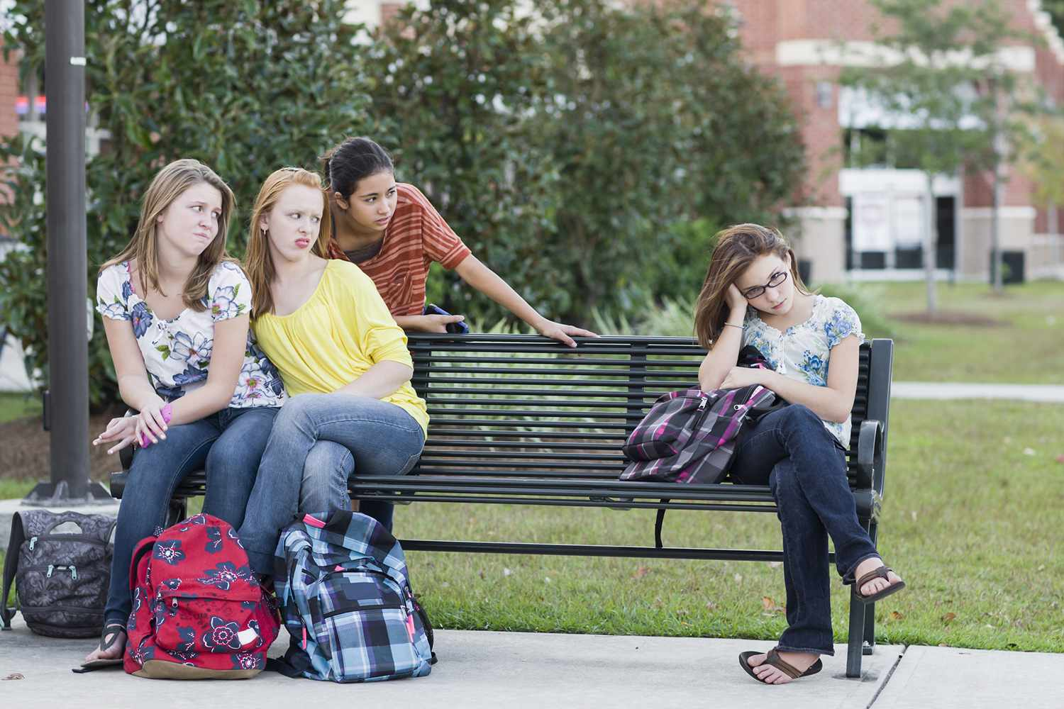 3 girls glaring at a 4th girl, all on a park bench
