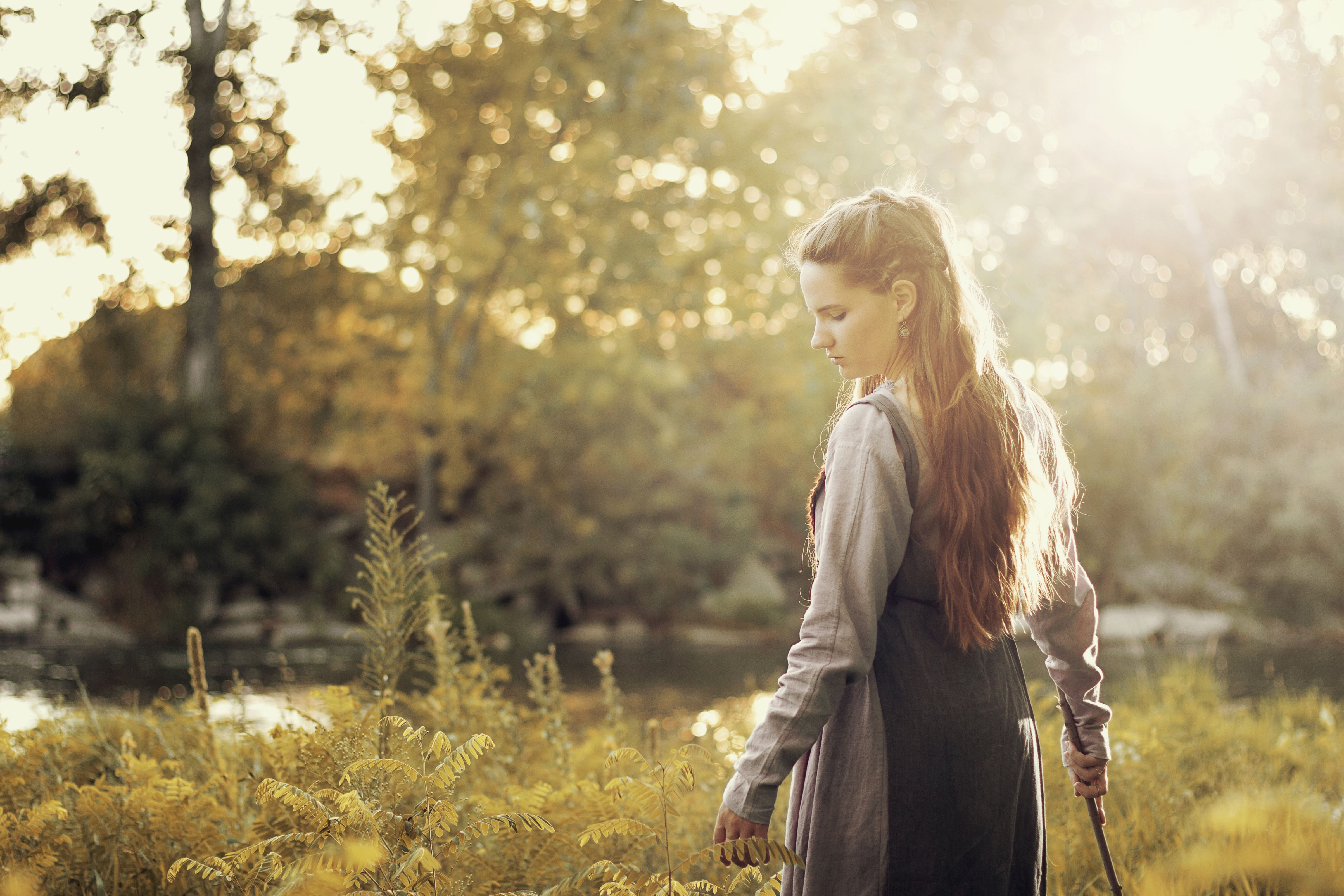 Young woman with long hair in period viking costume looks down, turning, outdoors and sunlit