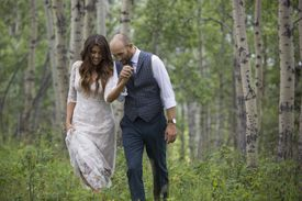 Affectionate bride and groom holding hands and walking in woods.