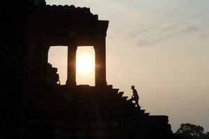 A visitor is silhouetted by the setting sun as he climbs the steps of Angkor Wat