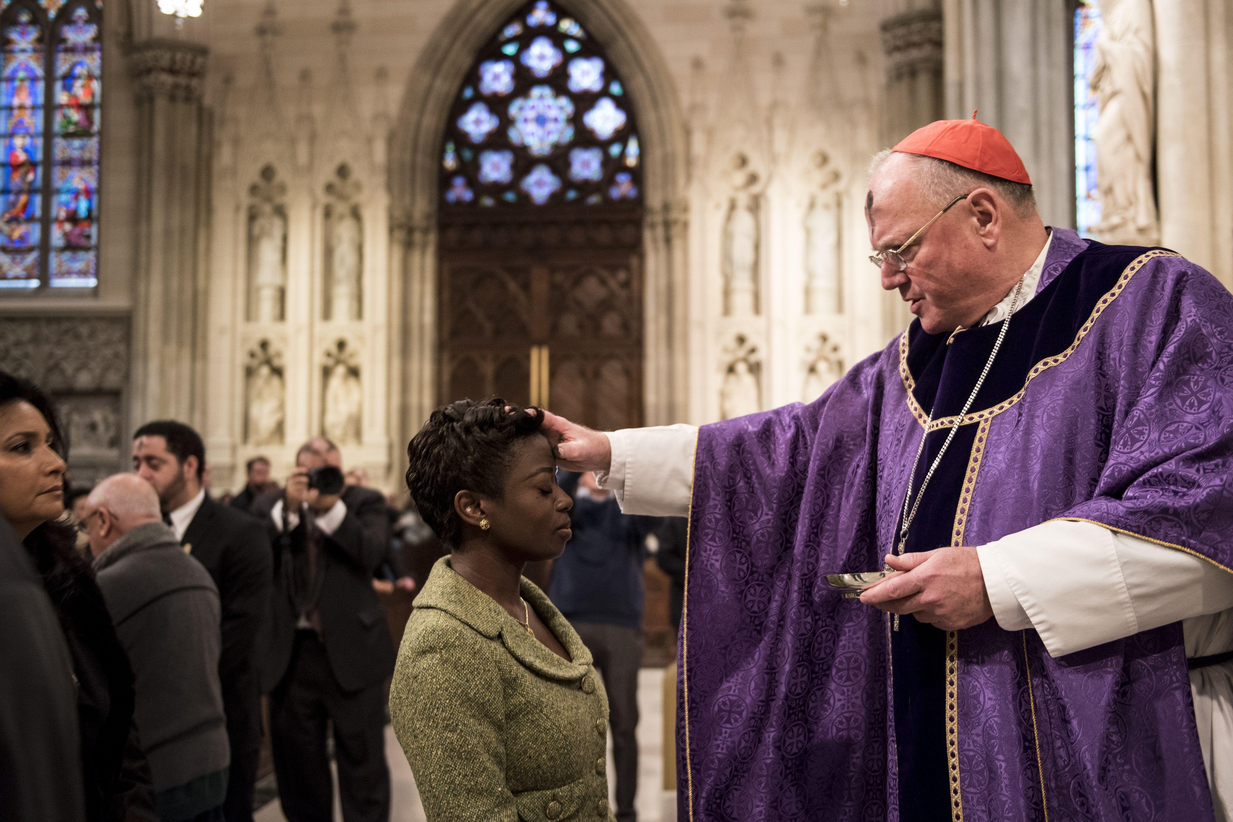 Priest applying ash cross on mass attendant.