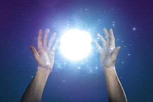 Hand supporting abstract glow of light and stars