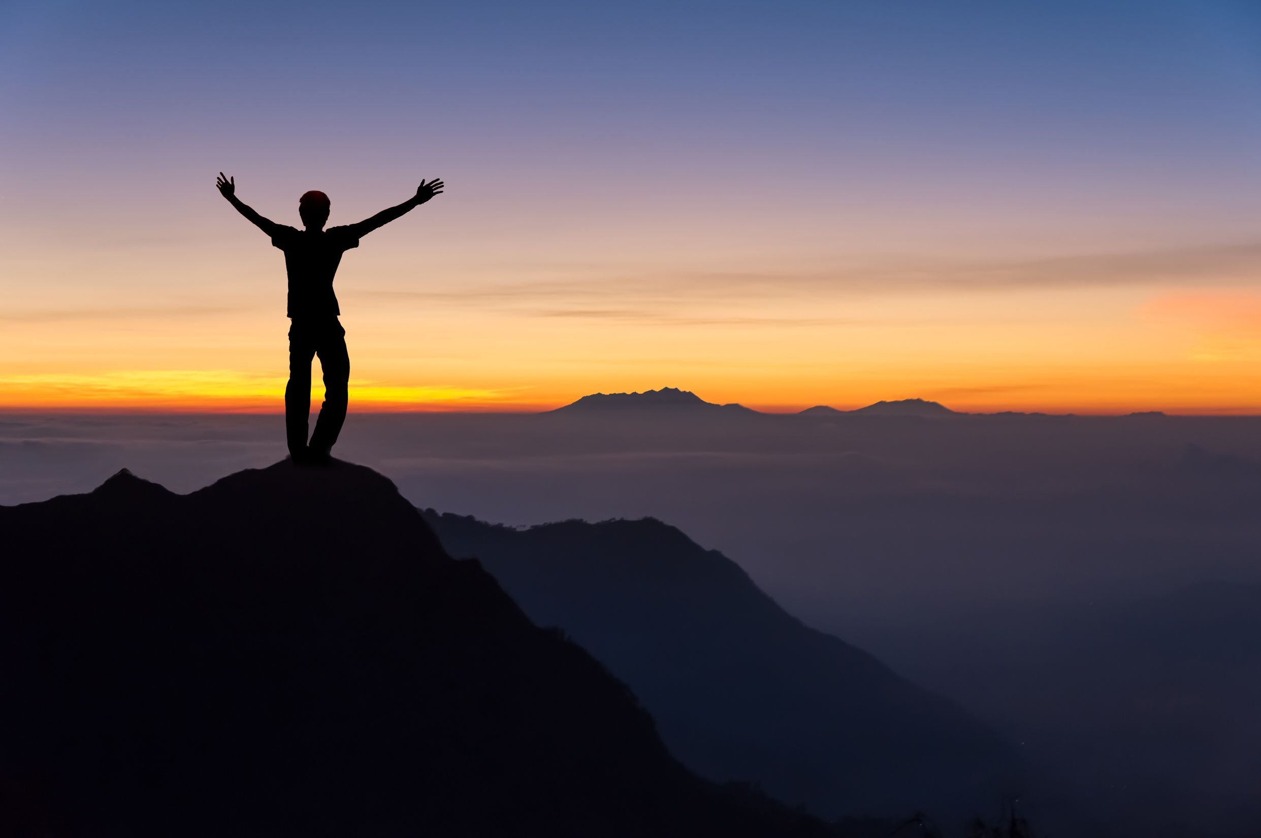 Person on cliff at sunset with arms up