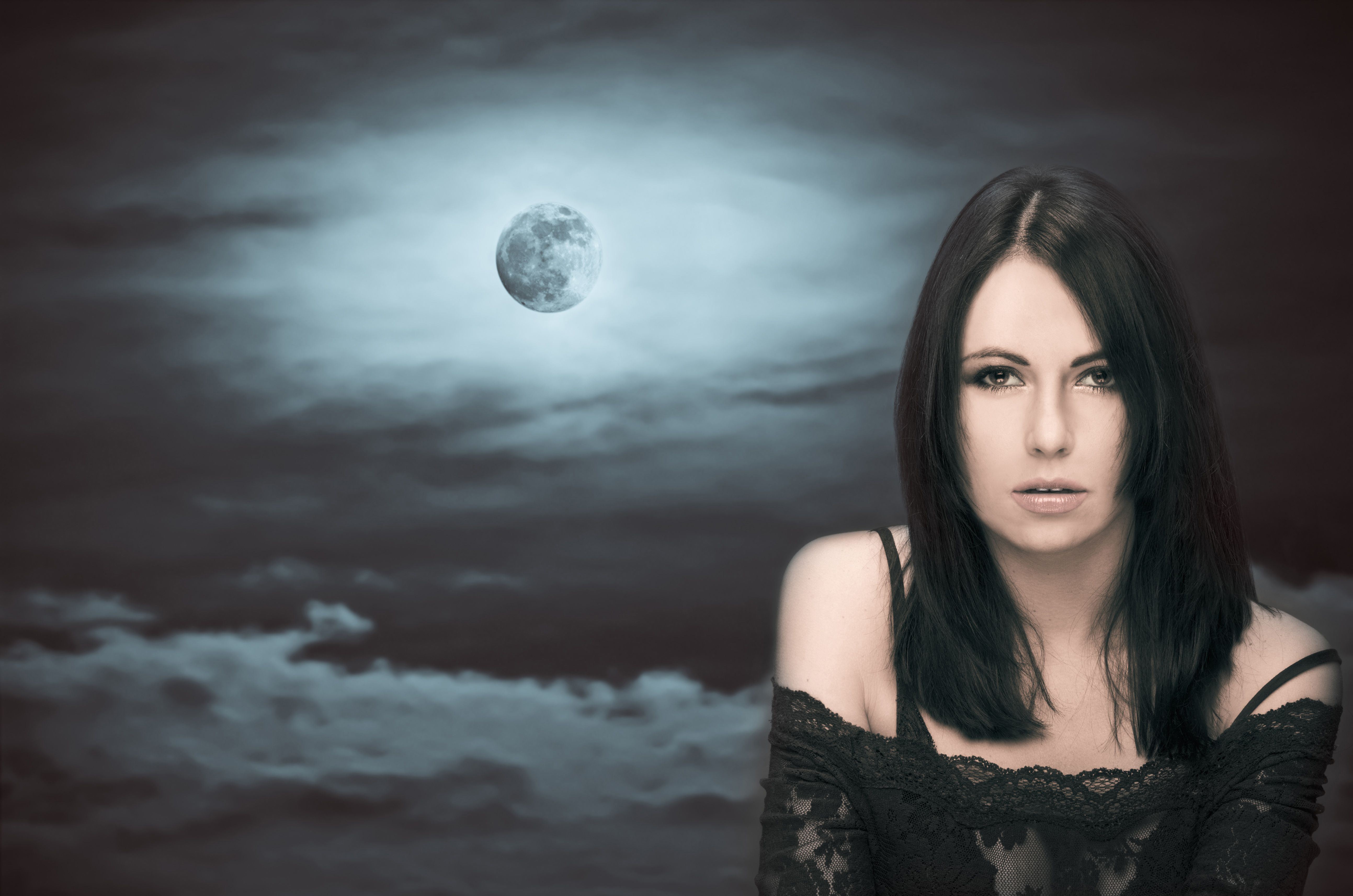 Woman in front of full moon