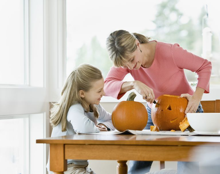 Mother and daughter carving pumpkins at home